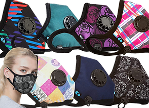 A blonde woman partly facing the camera, wearing a face mask with a black and gray rose design.  2 rows with 7 other masks are above and next to her, each mask a different pattern or color.