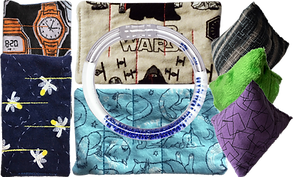 4 cloth marble mazes- one with waches on a black backround, one with fireflies on a dark blue background, one star wars theme, and one with cats on a light blue background.  Over top of the star wars and cat mazes is a plastic liquid filled bangle barcelet with blue beads inside.  To the right are 3 cloth and stuffed pyramid sensory toys.