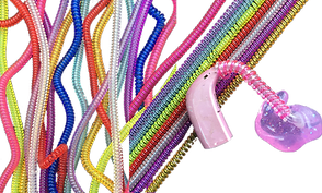 a pink hearing aid with pink plastic tubing curled around it, and 2 batches of various colored plastic twirly tubes.