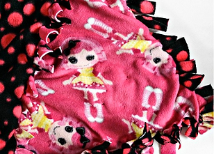 A fleece pink and black blanket with girls in dresses on one side and pink polka dots on the other with tied fringe ends.