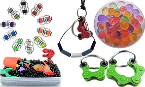 A circle of double ring fidget toys in rainbow colors, a plastic tub with black water beads, plastic dinosaurs and other items, a chewy necklace in gray black and blue bars, a bike chain fidget necklace, 2 sizes of lime green bike chain fidget keyrings, and a bowl of multicolored water beads.