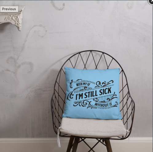 "A bright blue Pillow rests on a wirebacked chair against a gray wall.  The pillow has a black swirly design.  Text within the design reads, ""With my IV.... I'm Still Sick... Without it."""