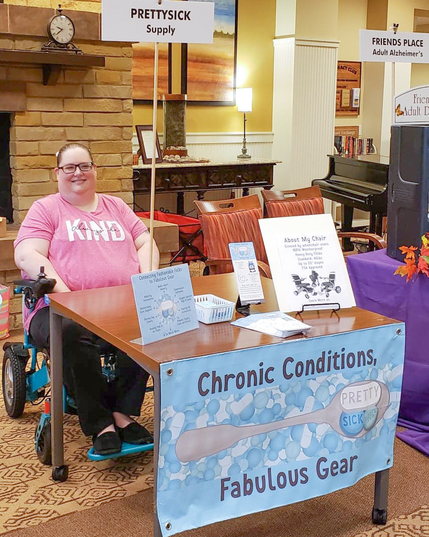 "A photo of SarahCate behind a small table bearing a banner for PrettySick Supply.  On the table are rack cards, flyers and a graphic about what PrettySickSupply does.  SarahCate is in her teal powerchair with her hair up in a ponytail.  She's wearing a pink shirt that reads, ""Always be Kind"""