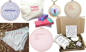 "Various embroidered products with spoonie and illness themes.  Hooped embroidery reading ""Spoonie"", ""Pajamas all day"", and ""Rest Your Bones"", a necklace with an embroidered semicolon, a zippered bag embroidered with ""Happy Pills!"", and a small cardboard box with various self-care goodies, and a pair of white undies embroidered with ""I am enough"" on the front."
