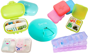 "5 styles of Pill organizers in vaying colors.  Some with cartoon animals on the front, 2 printed with the word ""smile"" (one oblong and one round), a stack of 3 square boxes with a first-aid style cross on front in pink, blue, and red, with the same open beside them, and a stack of three long rectangular organizers in pink, blue, and clear."