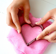 A glop of pink slime being cut into by a heart shaped cookie cutter.