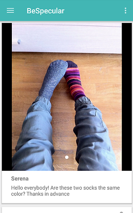 "Screenshot of BeSpecular App, a white screen with green bar across the top. In the bar are 3 lines to indicate a drop down menu at the far left, the word, ""BeSpecular"" next to them, and to the far right 3 vertical dots indicating a settings menu.  In the center of the screen is a photo of someone's legs in jeans with feet wearing two different socks.  Below the photo, text reads, ""Serena.  Hello Everybody! Are these two socks the same color? Thanks in advance."""