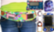 A person's waist area wearing a patterned belt that has 2 windows showing different diabetic meters inside.  Next to it are various meters and pods decorated with different patterned decals.