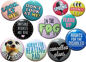 "11 1"" Buttons of various colors.  Messags include, ""Look a Me!"" ""Don't Look at Me!"" ""Spoonie,"" ""Flae Up"" ""Invisible Diseases Are Real,"" ""In the Fog,"" ""Rights for the Disabled,"" ""Self-care"", ""Horny fo Heating Pad,"" and ""Cancelled Plans"""