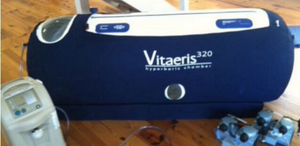A slightly blurry photo of a portable hyperbaric 02 chamber set on a wood floor.