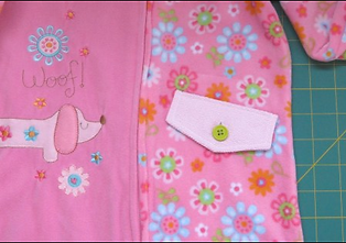 A pink baby's outfit with a small dog embroidered on one side, and flowers on the other with a small pocket.