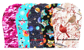 5 different ostomy covers in a variety of fabrics.  They are a pink camo, a blue with birds and butterflies, a space theme, black with multi-colored cartoony owls, and a cream color with branches and realistic bird illustrations in reds and browns.