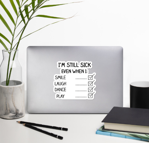 """A silver laptop on a desk surrounded by decorative plant leaves, a book, and pencils.  The laptop is open and on the back cover is a black and white sticker with a checklist that reads, """"I'm still sick even when I: Smile, Laugh, Dance, Play""""  Each item has a box with a checkmark next to it on the right side."""