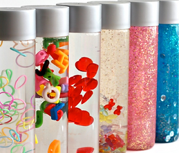 6 different clear bottles with silver tops.  Each bottle has different elements inside- colorful bands, plastic letters, red globs, white, pink and blue glitter.