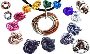 A ring of chain maille knotted fidget toys in a rainbow of colors.  Inside the ring is a chain mail fidget necklace in copper and silver, around the edges of the ring are other metal fidget toys and rings.