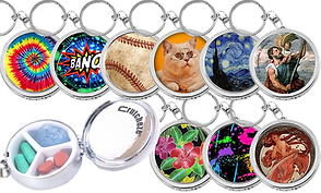 9 round keychain pillboxes shown closed and 1 shown open to show the divided interior compartment.  The keychains all have different designs: rainbow tie dye, a comic book bang, a closeup of a dirty baseball, a fat cat wearing glasses, van gogh's starry night, a painting of St. Christopher, 3 hawaiin style flowers, neon paint splatters, and an art-deco style woman. with red hair.