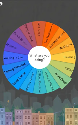 """Screenshot of Buddhify App, a dark gray screen with small colorful street of apartments at the very bottom. In the center is a large circle made up of a rainbow of small slices.  In the center is a white circle that reads, """"What are you doing?""""  Each slice of the circle has a different choice like, """"Work Break, feeling Stressed, Being Online, Waking Up, Eating, Can't Sleep"""" and more."""