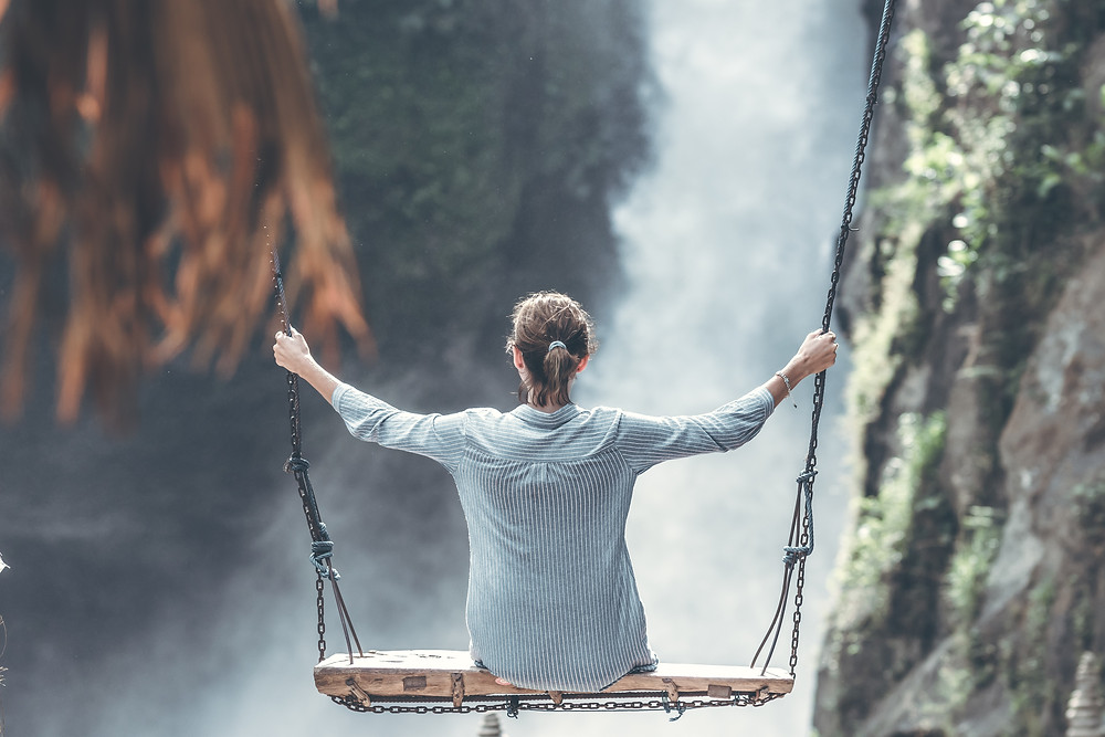 Woman on a wooden swing overlooking a waterfall as is she's pondering the world.
