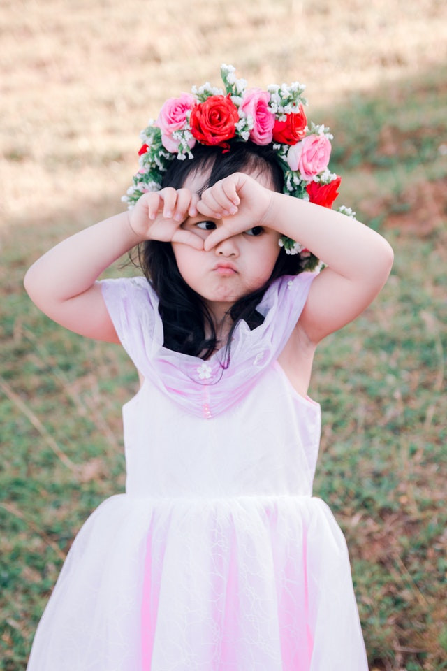 flower girl for wedding with a pouty look on her face covering her eyes with hands