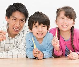 歯ブラシを持っているお父さんと男の子と女の子