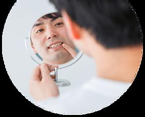 鏡で歯をチェックする男性