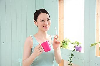歯ブラシとコップを持つ女性