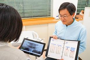 歯の状態を患者さんに説明する医院長
