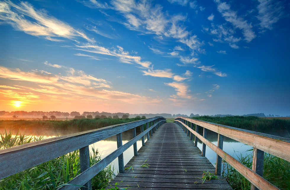 Wooden bridge surrounded by beautiful sunset over water