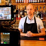 a man in apron being filmed on camera behind a bar