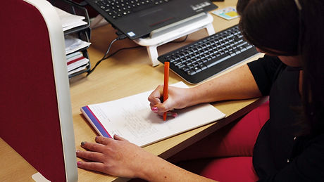 a woman at a desk writing on a notepad
