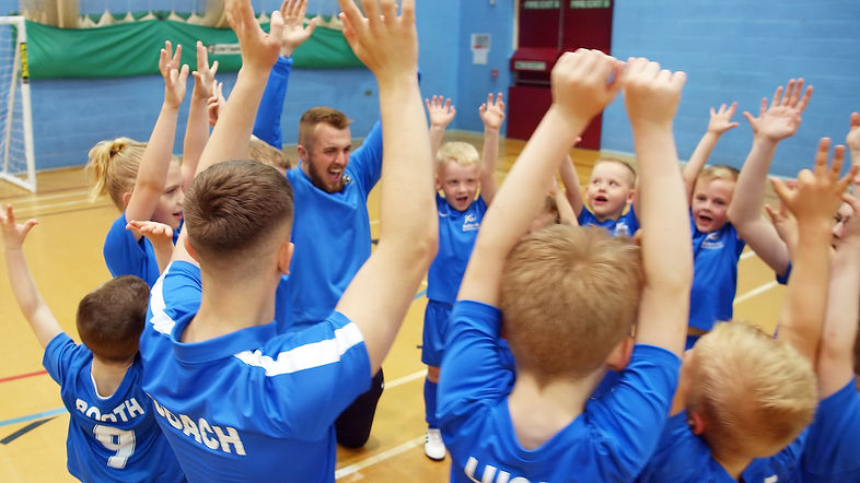 football group with kids arms up in the air