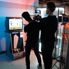 filming the national arcade museum with two men stood behind a camera looking at a TV screen