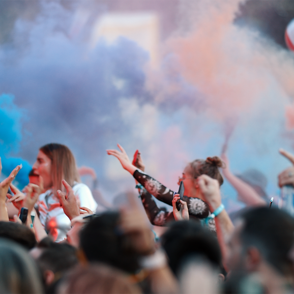 a group of people partying with coloured paint creating a vibrant background