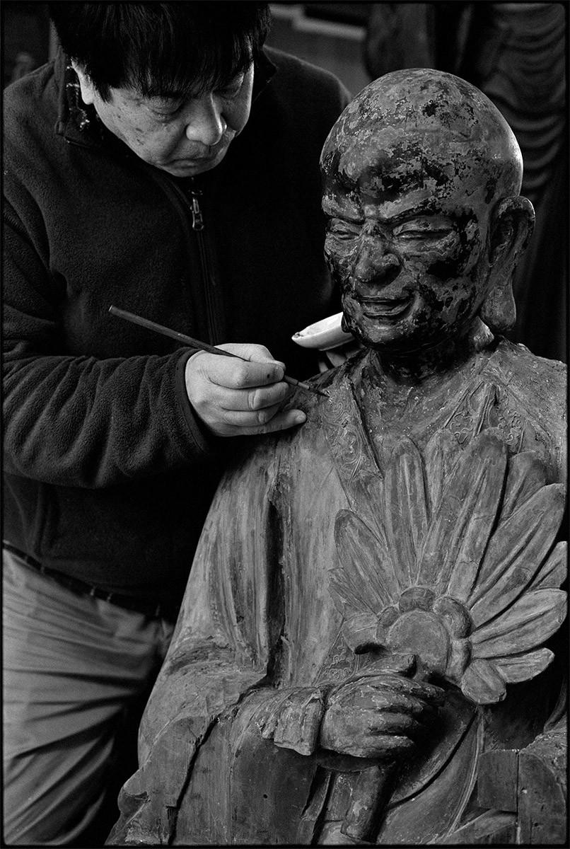 東京・目黒の五百羅漢寺には現在305体の羅漢像たちが存在する。この羅漢像は過去の災害で被災しバラバラになってしまった 別々の像の部材を組み合わせて一体にしたものだ。仏像修復家の長井武志氏は、数奇な運命を辿ったこの羅漢像を、像の個性と してとらえ後世に伝えていくための修復を施していた。(撮影・長井氏の工房にて)