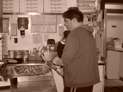 Tony cutting a pizza