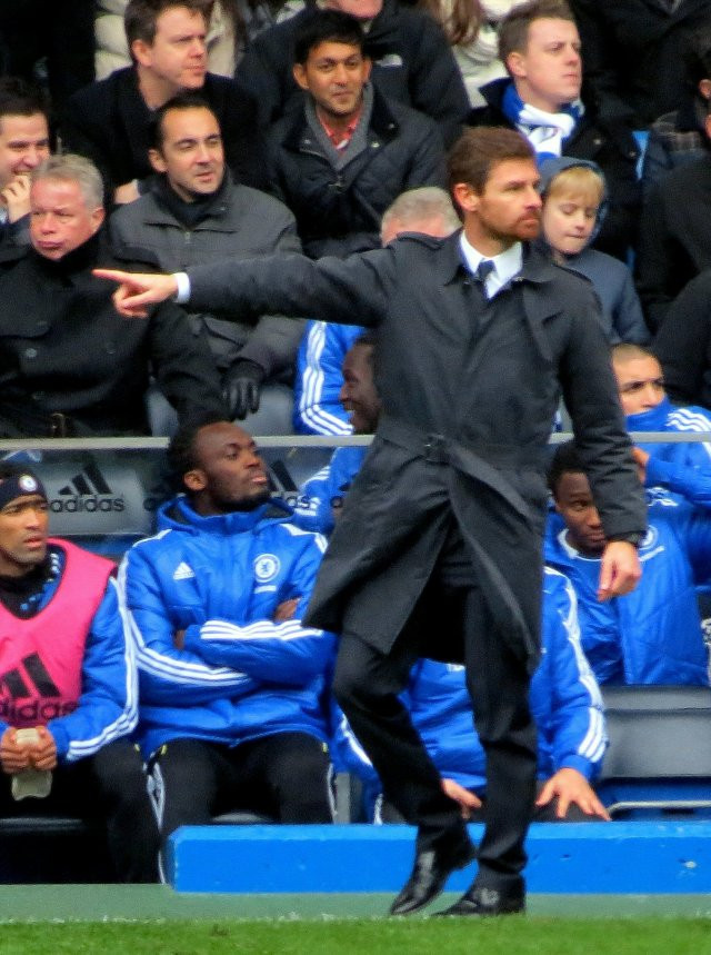 Andre Villas-Boas as Chelsea manager pointing to one of his players where he wants the ball to be played with the Chelsea subs in the background and the Stamford Bridge crowd looking on.