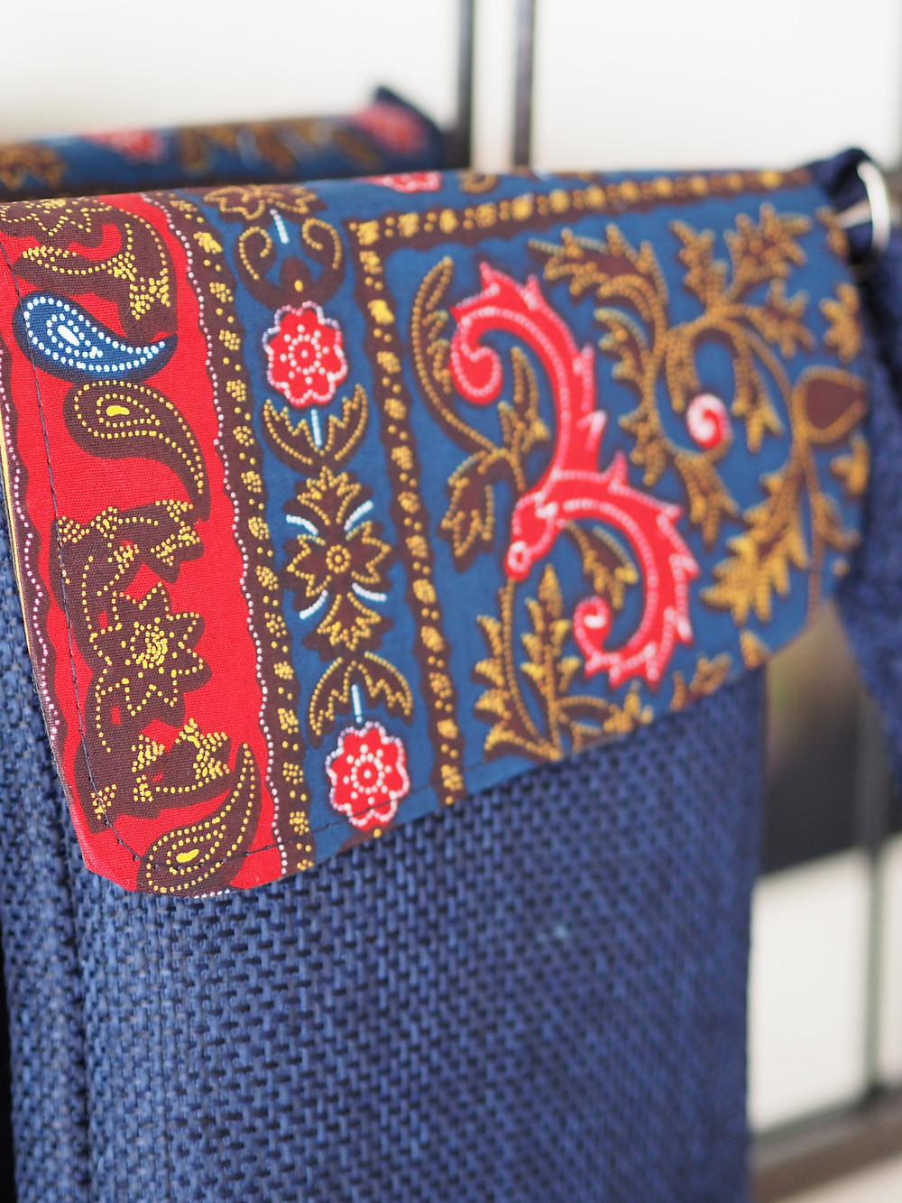 Kenyan kikoy fabric adorning a handmade navy handbag