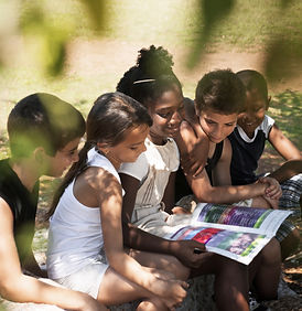 Group of diverse children reading an educational magazine