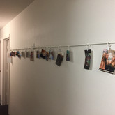 Curtain rod converted into photo display in hallway. Repurpose your oversized curtain rod for a wall length picture display by adding clipped up copies of your favorite memories. Photo by Chase Davis.