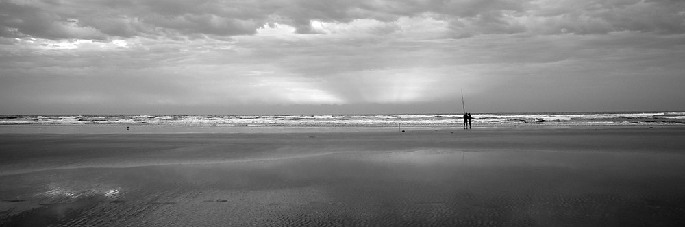 Surf fishing at sunset. Venus Bay Victoria. Black and white image.