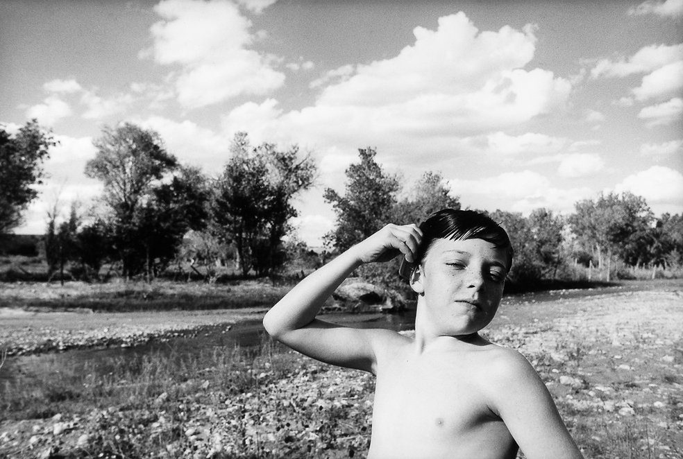young boy combing hair while standing beside a river mimicking John Travolta