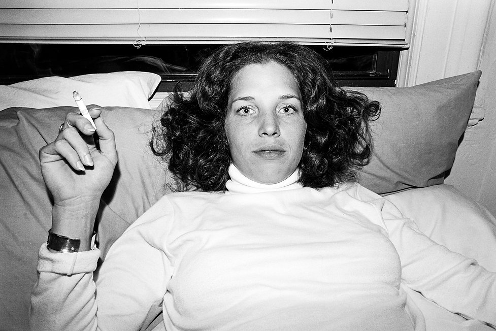 Woman with white turtleneck smoking a cigarette laying in bed