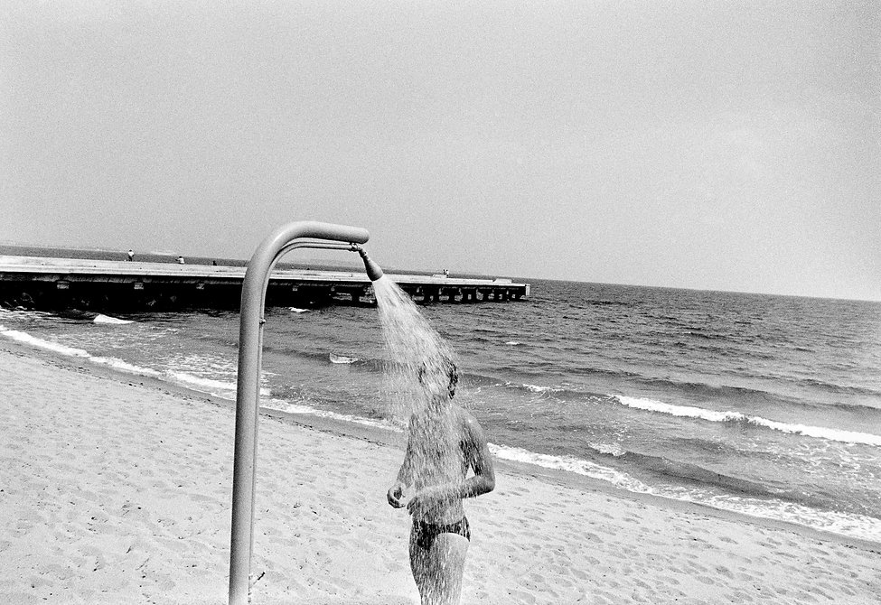 Man in outdoor shower on the beach, Plage Midi, Cannes