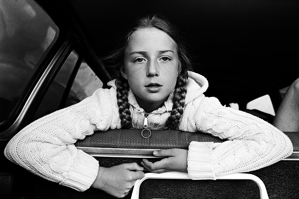 girl in rear seat of station wagon looking out the rear open hatch