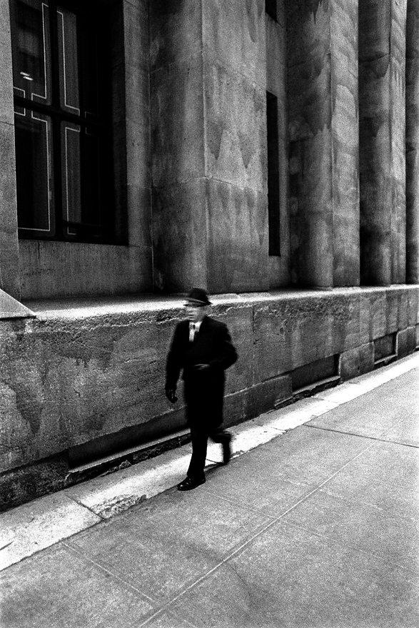 business man walking near wall street new york city
