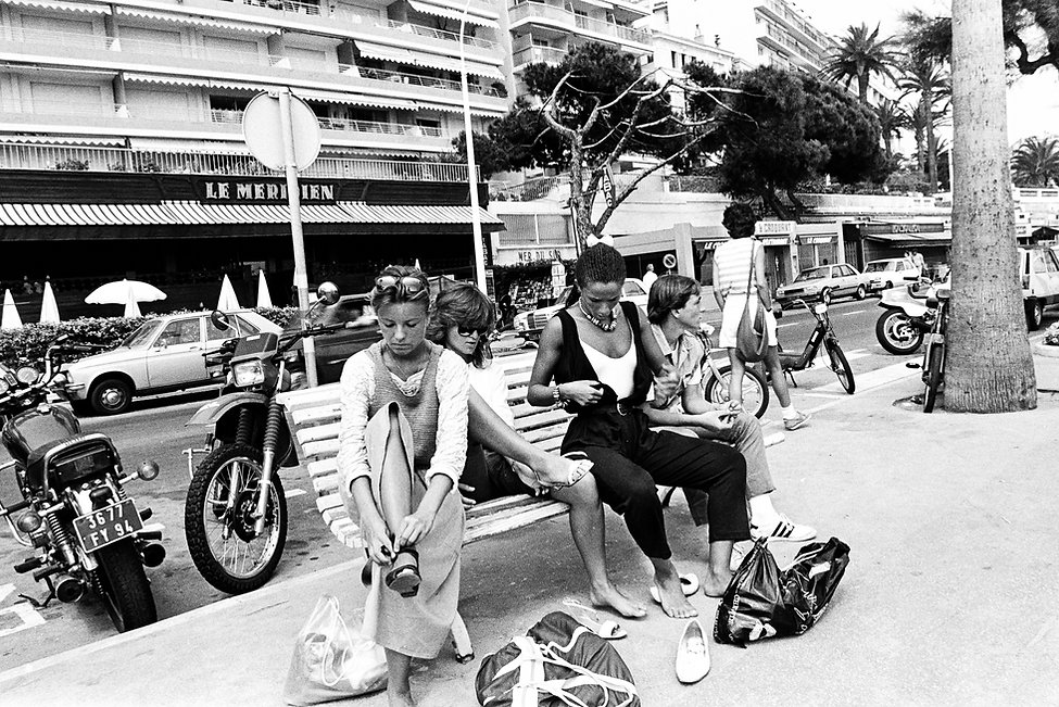 Women getting dressed on bench after topless sunbathing on Plage Midi, Cannes