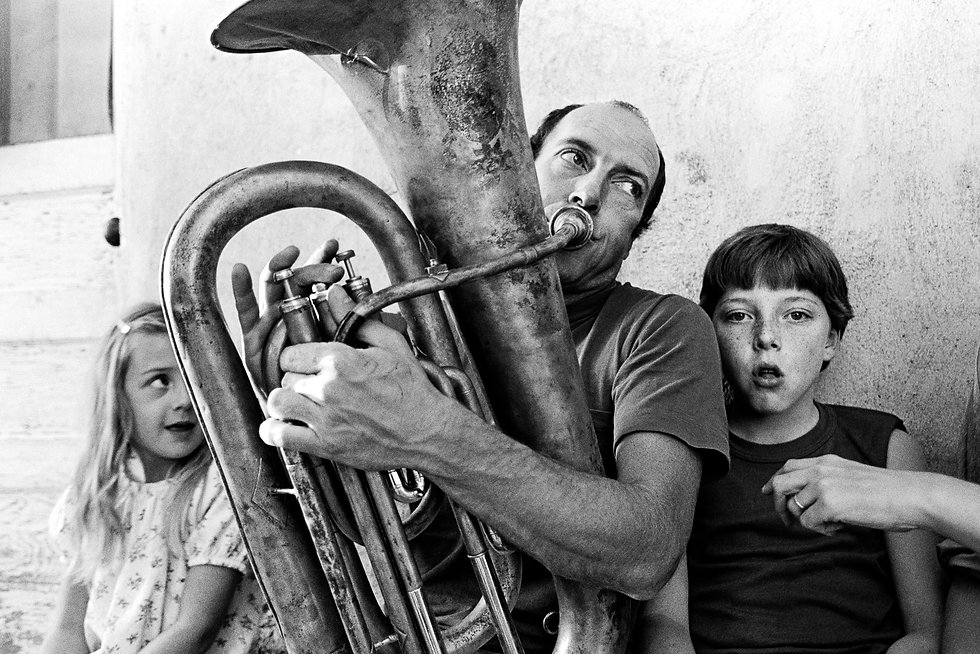 man playing tuba with two children