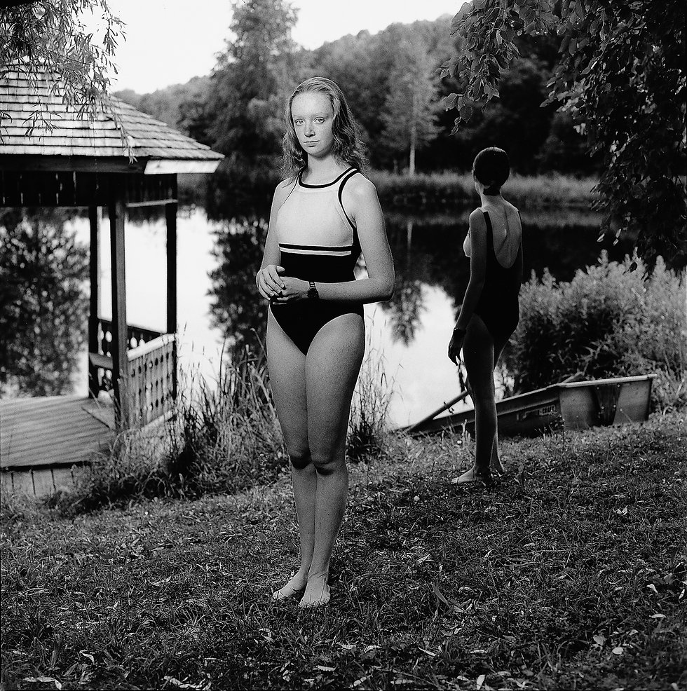 Two young women in bathing suits standing beside a pond