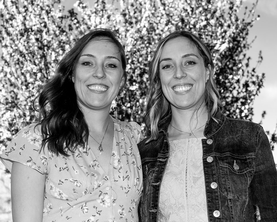Identical twins with white teeth smiling at camera
