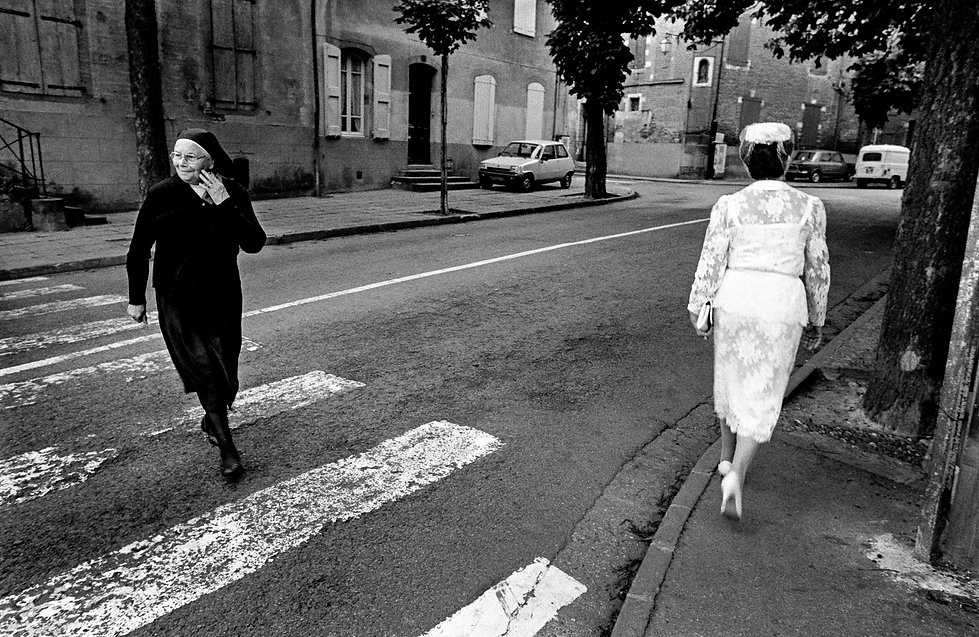 nun in habit and woman wearing white dress on city street in Carcassone, France 1984